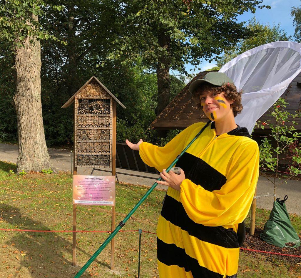 Korkeasaaren opas kimalaisasussaan hyönteishaavin kanssa ötökkähotellin edessä.