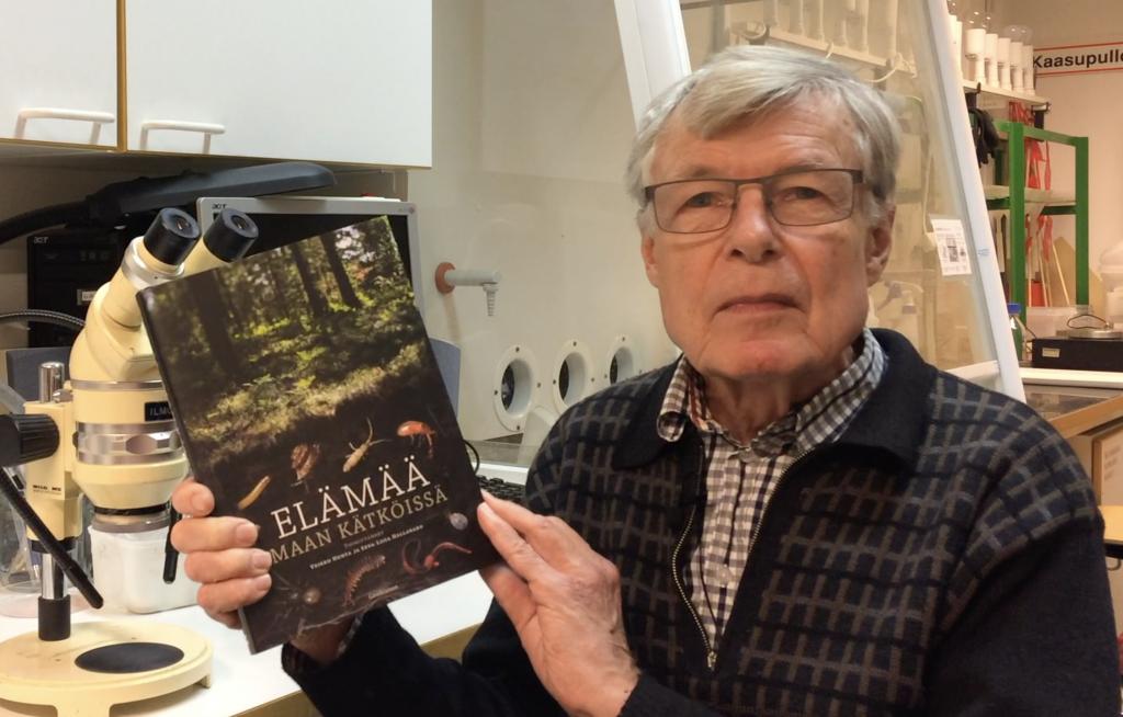 Veikko Huhta näyttää laboratoriossa Elämää maan kätköissä -kirjaa.